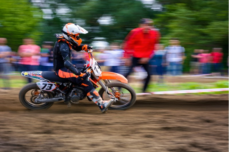 Uzhgorod, Ukraine - May 21, 2017: MX rider turns on a corner. Motion blur with flying dirt. TransCarpathian regional Motocross Championship