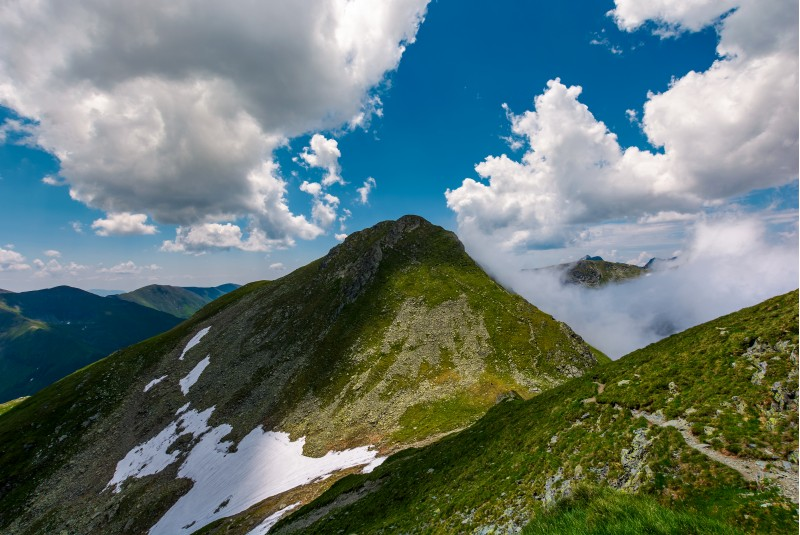 Peaks of mountain ridge among the clouds. Mighty formations with rocky tops and grassy hills. beautiful summer nature scenery on high altitude