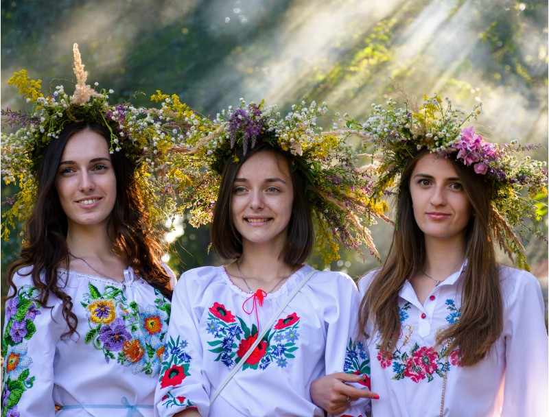 Uzhgorod, Ukraine - 07 Jul, 2016: Portraits of three Young ladies with traditional wreath on their heads. background of park with light coming through smoke. Popular holiday in Slavic culture