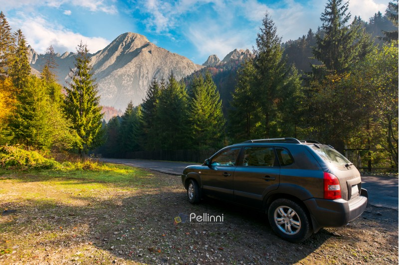 SUV on countryside road in High Tatra mountains. lovely transportation scenery at sunrise in autumn. disover Slovakia travel by car concept. composite image
