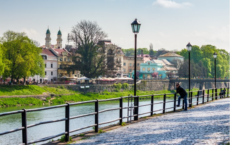 Uzhgorod, Ukraine - April 13, 2016: beautiful cityscape of the old central part of a town on the river Uzh in springtime, viewed from the Kyiv embankment with metal fence and lanterns