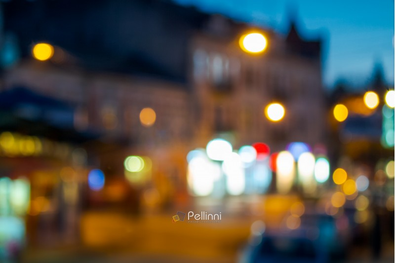 beautiful evening scenery of european town. street with bright lanterns. abstract blur background. bokeh effect