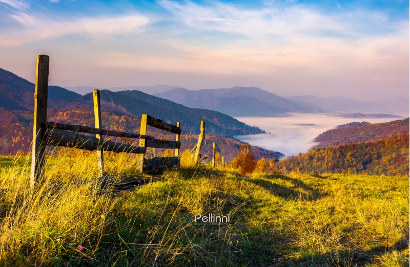 beautiful mountainous landscape with wooden fence. lovely autumnal scenery at sunrise with gorgeous sky over the valley full of fog