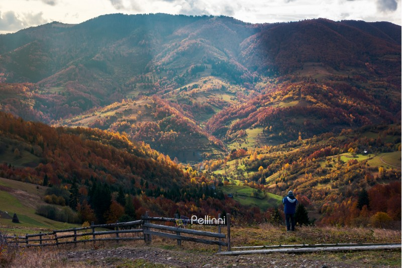 undefined person on the edge of a hill looking in to the distant rural valley. beautiful nature scenery in autumn