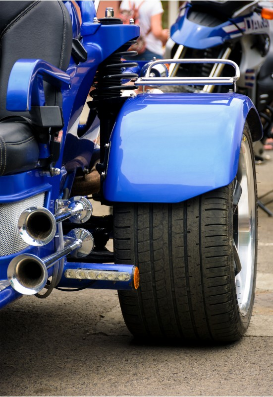 rear side of a blue motorcycle. lovely detail shot of lights and shiny exhaust pipes