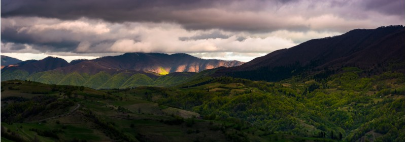 panorama of cloudy sunset in mountainous countryside. beautiful springtime landscape with ridge in the distance. rural area on grassy slopes on rolling hill in the foreground