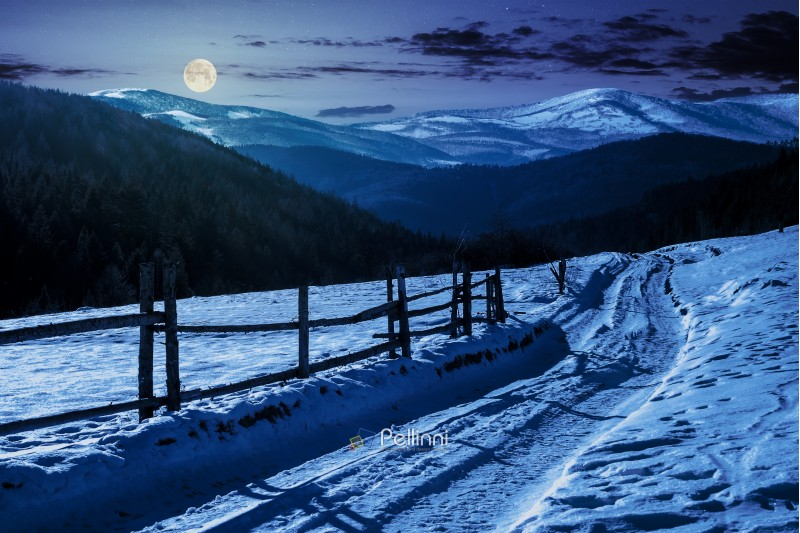 country road in to the winter mountains at night in full moon light. wooden fence along the road. composite image
