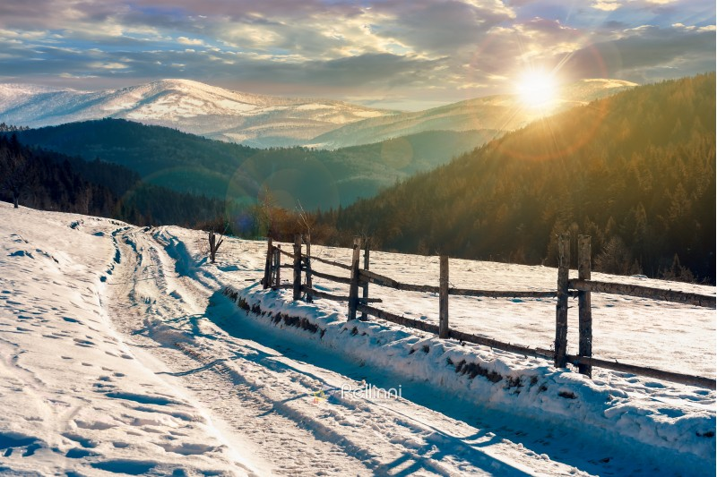 country road in to the winter mountains at sunset. wooden fence along the road. composite image