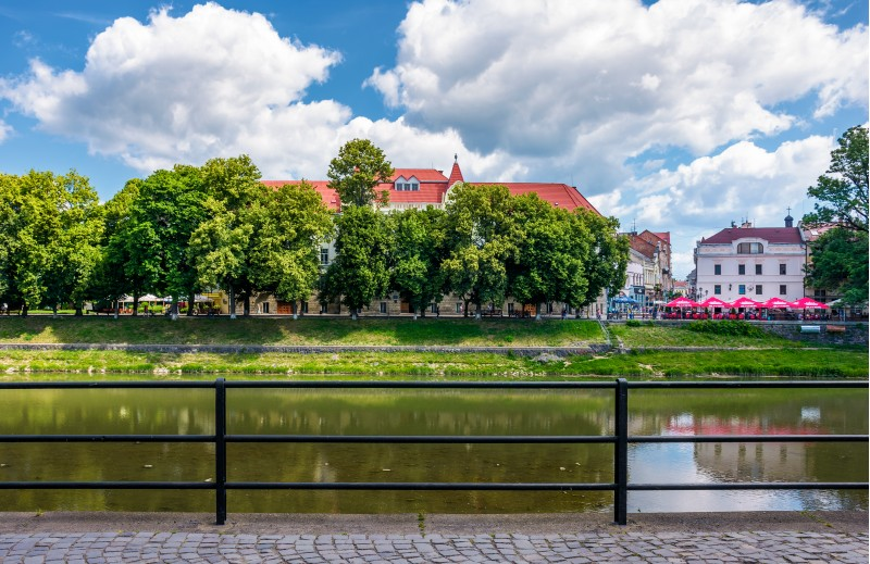 Uzhgorod, Ukraine - Jun 15, 2017: embankment of Uzh river in summer. Beautiful architecture and blossoming linden trees on fine weather day. Korzo street can be seen in the distance