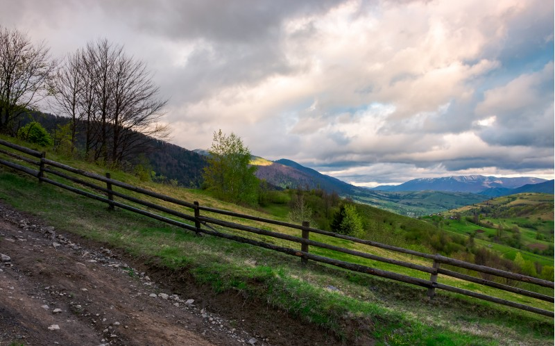 fence on a hillside of mountainous countryside. lovely rural scenery in springtime