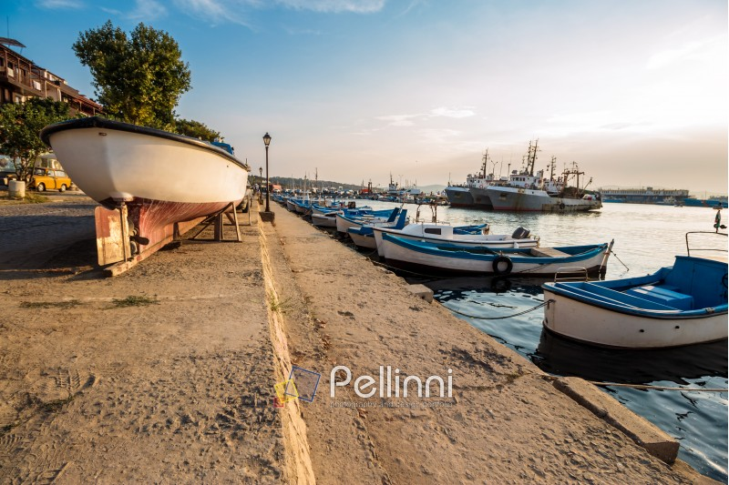 SOZOPOL - AUGUST 16: fishing boats at sunset on August 16, 2015 in Sozopol, Bulgaria. small fishing boats and few big one docked near embankment in port of Bulgarian town Sozopol in evening light