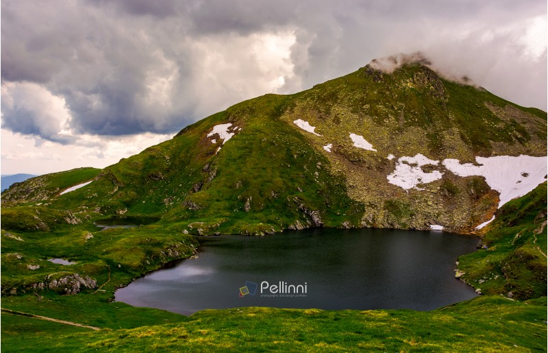glacier lake Capra at the foot of the mountain. lovely summer scenery on a cloudy day. popular travel destination in Southern Carpathian mountains of Romania