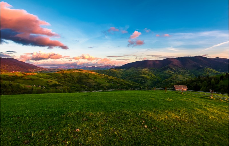 gorgeous mountainous countryside at dusk. beautiful landscape with rural fields, fence and  woodshed. pink clouds on a spring blue sky over the mountain ridge in the distance