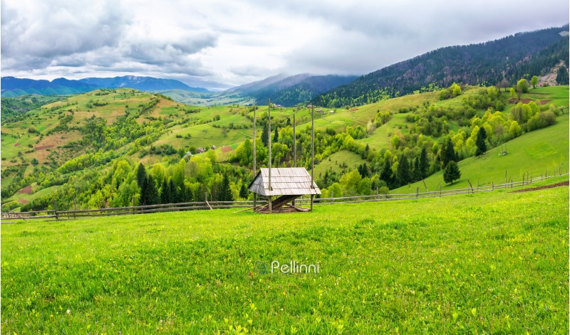 hay shed on a grassy field in mountains. beautiful countryside landscape in springtime. cloudy forenoon. village on the distant hills