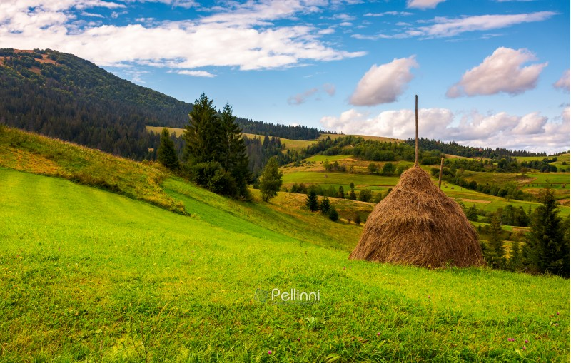 haystack on a grassy meadow in mountains. beautiful landscape under the azure sky with gorgeous cloudscape