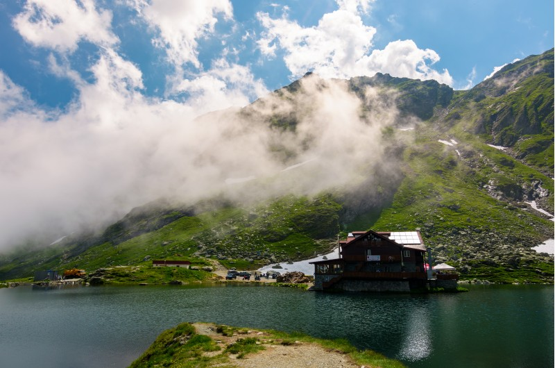 lake Balea of Fagaras mountains. lovely summer landscape with low clouds around the peak