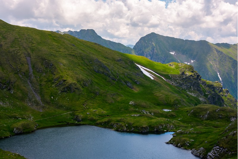 lake Capra in Fagarasan mountains of Romania. beautiful summer scenery on a cloudy day. Popular tourist destination for Hiking.