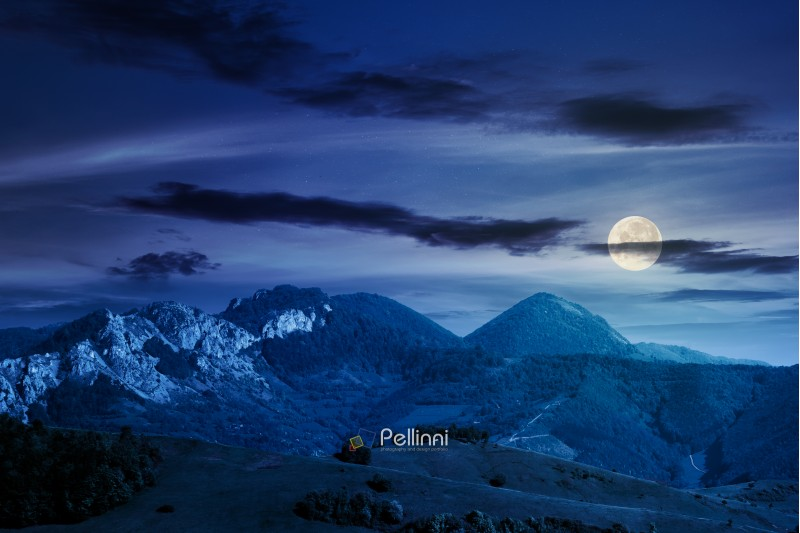 landscape in mountains with rocky formations. grassy meadows, forested hills and huge cliffs. wonderful nature scenery. beautiful weather at night in full moon light in springtime