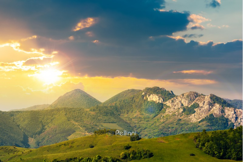 landscape in mountains with rocky formations. grassy meadows, forested hills and huge cliffs. wonderful nature scenery. beautiful weather at sunset in springtime