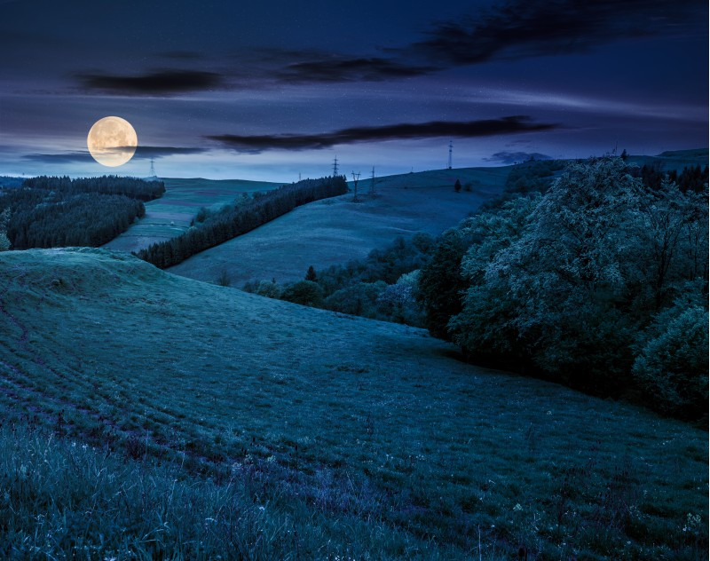 lovely countryside with grassy hills at night in full moon light. beautiful nature of Carpathian mountains in springtime