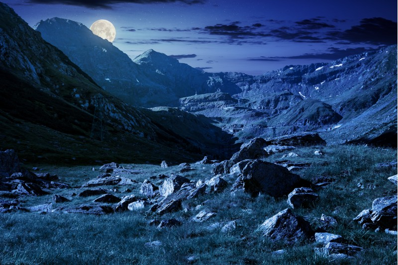 lovely scenery of Transfagarasan road in valley at night in full moon light. rocks on grassy meadow and slopes. half of the valley in shade of mountain ridge