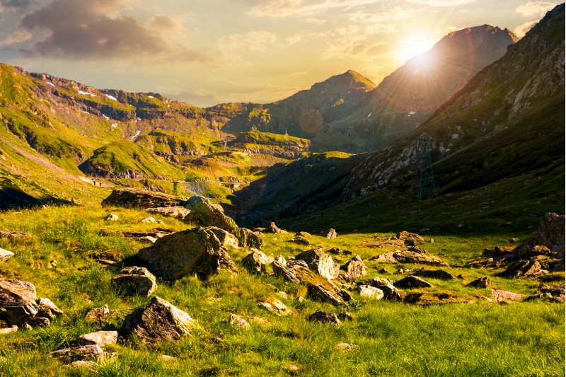lovely scenery of Transfagarasan road in valley at sunset. rocks on grassy meadow and slopes. half of the valley in shade of mountain ridge