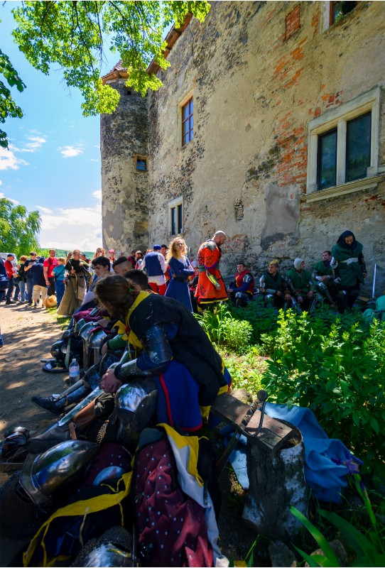 Chynadiyovo, Ukraine - May 27, 2017: medieval culture festival Silver Tatosh. Location St. Miklos Castle. Knight participants have rest under the castle wall in shade of tree