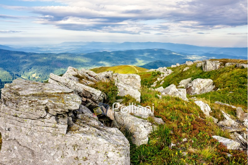 mountain landscape. stones in the grass on the hillside going into the distance under a blue sky