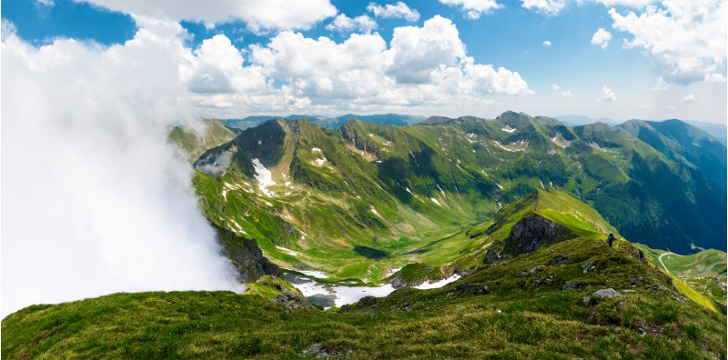 mountainous panorama with rising clouds. beautiful landscape with some snow on grassy hillsides. popular destination for hiking in Fagaras mountains of Romania