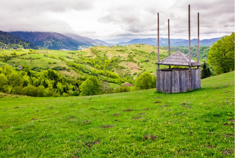 old wooden hay shed on grassy hillside. beautiful scenery of mountainous rural area in springtime
