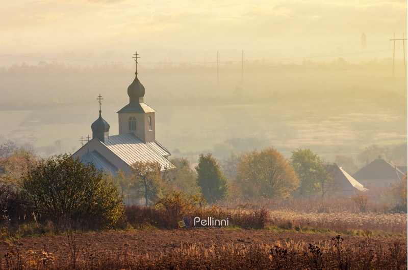 orthodox church on a hill above the foggy rural valley at sunrise. lovely countryside scenery in autumn