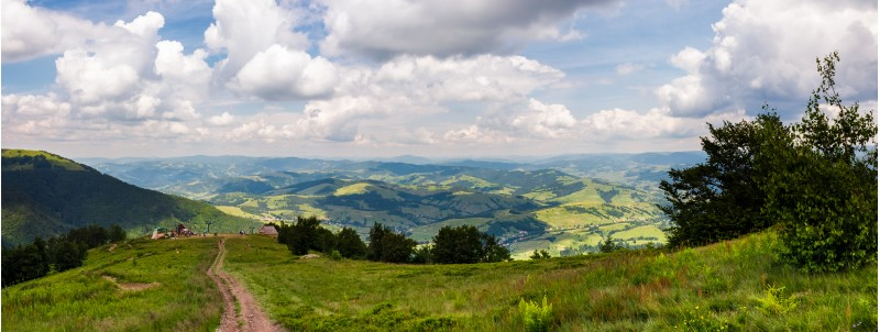 panorama of beautiful landscape in mountains. gorgeous view from Borzhava mountain ridge. road down the grassy hill to tourist base. wonderful summer weather with cloudy sky