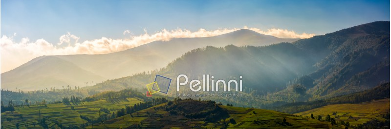 panorama of mountainous rural area at sunrise. Gorgeous autumnal morning weather with clouds above the mountains and fog in valley