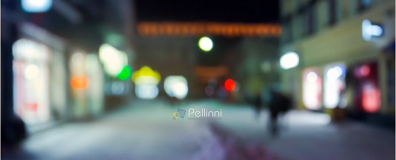 panorama of night street in winter. city light and glowing shop windows. christmas sales concept. blurred background