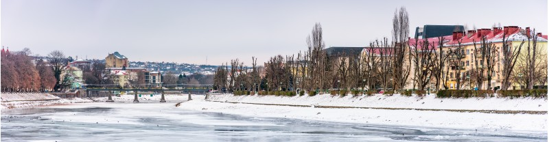 panorama of winter cityscape on the river Uzh. lovely travel background with Kyiv embankment, pedestrian bridge and some architecture of central part of old town Uzhgorod