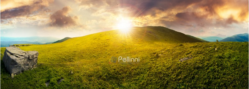 panorama with rock on the grassy hill in mountains. beautiful summer landscape in evening light. amazing nature scenery. dramatic cloudy sky at sunset