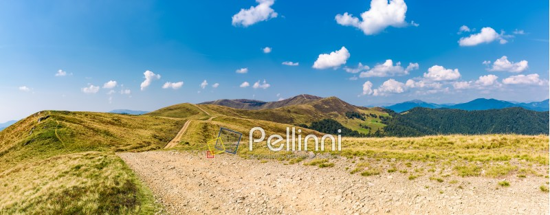 panoramic view of path through the mountain ridge. spectacular landscape in early autumn weather with fluffy clouds on the blue sky