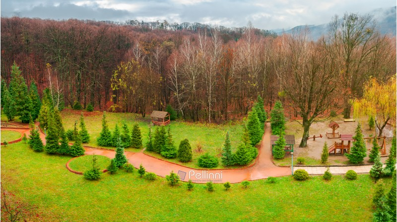 park with playground in autumn. gloomy rainy weather in mountains. green lawn and leafless forest in november