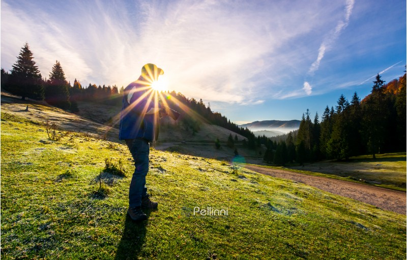 photographer in sunburst shooting foggy landscape. gorgeous scenery of Apuseni Natural Park in autumn at sunrise. wonderful adventure or job concept. blue sky with clouds