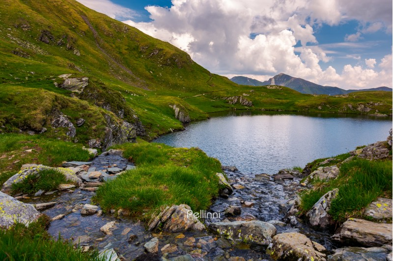 rapid streams flow to lake Capra in mountains. Fagaras mountain ridge under the gorgeous cloudscape in the distance. Beautiful summer landscape of Romania