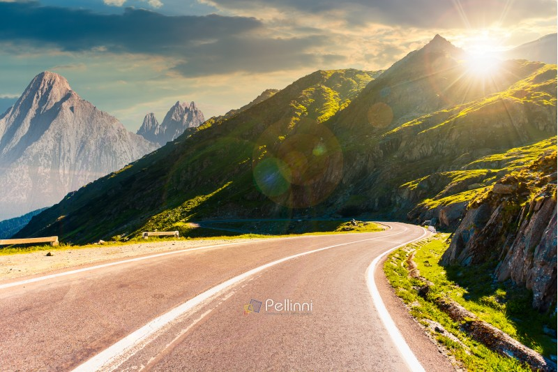 road in mountains with rocky ridge in the distance at sunset. composite image. travel by car concept