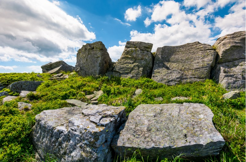 rocky formation on a grassy hill. beautiful summer scenery in mountains