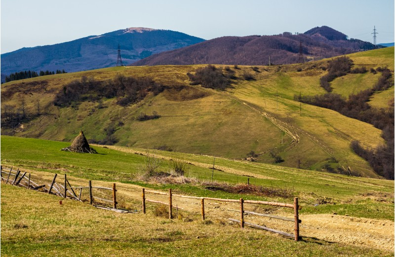 rural area on rolling hills in springtime. wooden fence and haystack near the road. lots of electric poles