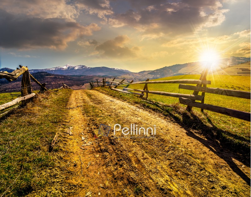 fence near the road through the  rural meadow in mountain region in spring time in evening light