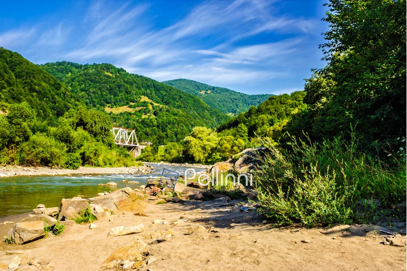 shore of a mountain river with stones and iron bridge among the forest in fural area