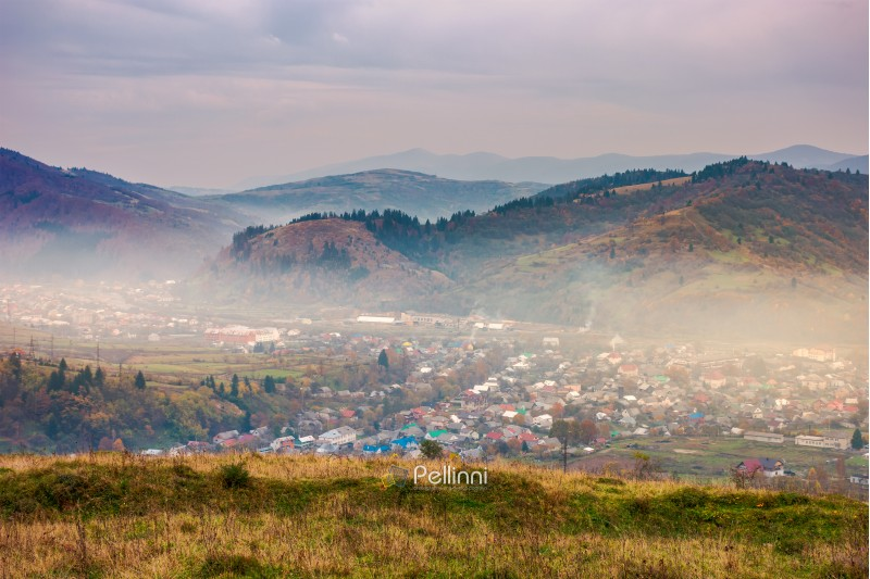 autumn countryside in mountains. small town in hazy valley. forested hills in fall colors. gloomy afternoon with overcast sky