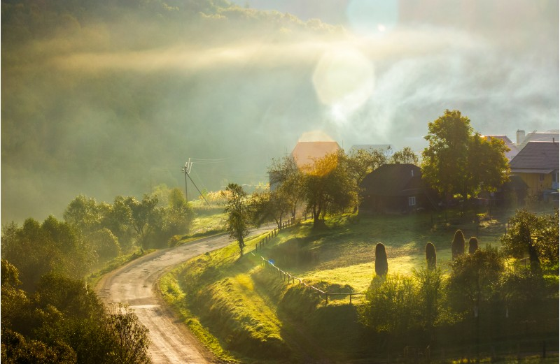 smoke and fog over the village at sunrise. beautiful rural scenery near the road in mountainous area