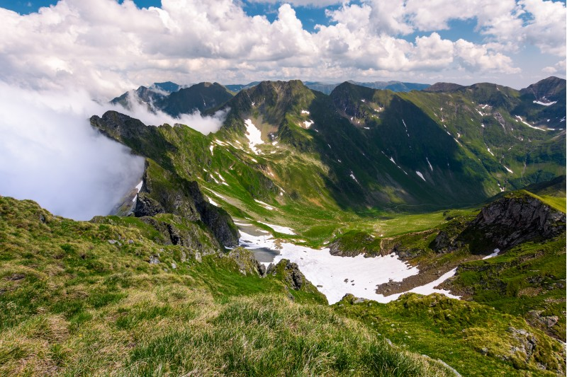 snow in the valley of Fagaras mountains. beautiful summer scenery on a cloudy day. dappled light on grassy slopes