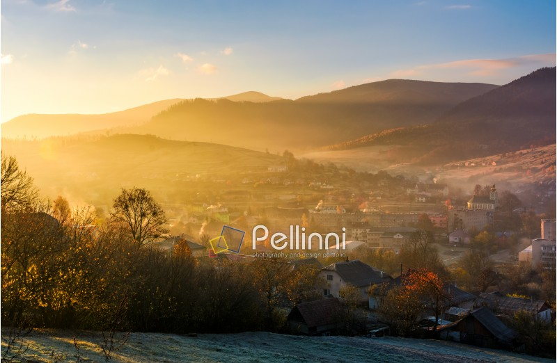 spectacular foggy sunrise in mountainous countryside. gorgeous autumnal landscape with village in mountains in fine weather