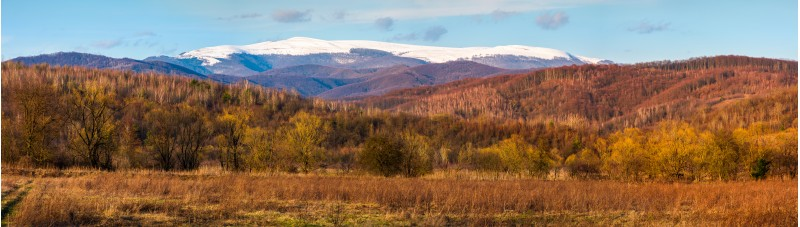 springtime countryside with snowy mountain in the distance. lovely panorama of Runa mountain in evening